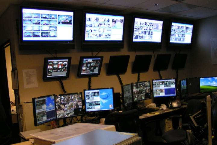 central monitoring room with multiple monitors displaying camera views