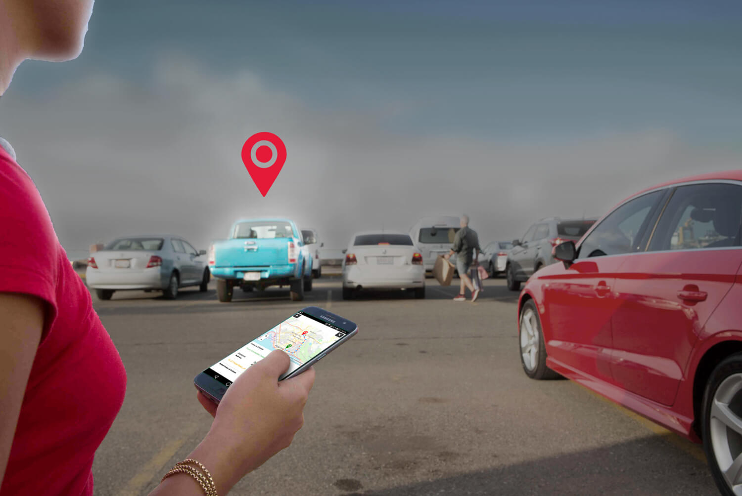 woman holding smart phone with vehicle tracking app while looking at her car